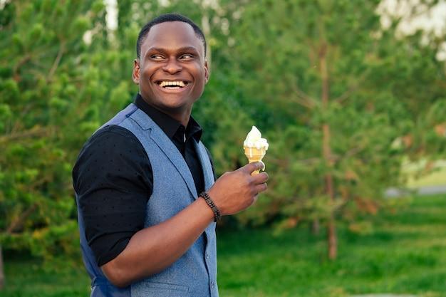 Ritratto di giovane e bel modello alla moda, uomo afro-americano in un elegante abito blu in un parco estivo intelligente uomo d'affari ispanico latino ragazzo nero che mangia gelato in un corno di cialda.