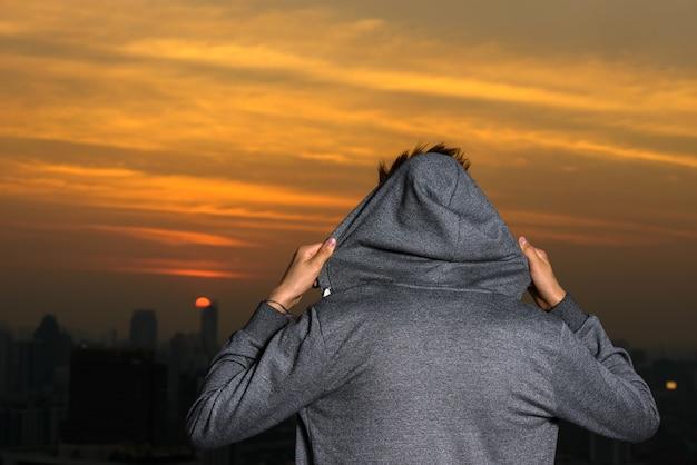 Ritratto di giovane adolescente bello contro la vista della città all'aperto
