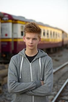 Ritratto di giovane adolescente bello presso la stazione ferroviaria