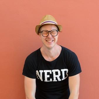 Ritratto di giovane turista bello come nerd su sfondo colorato all'aperto
