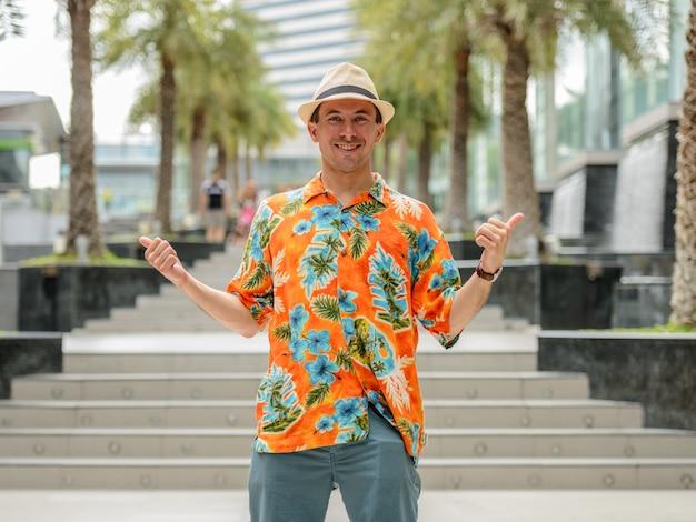 Ritratto di giovane uomo turistico bello al di fuori del centro commerciale della città
