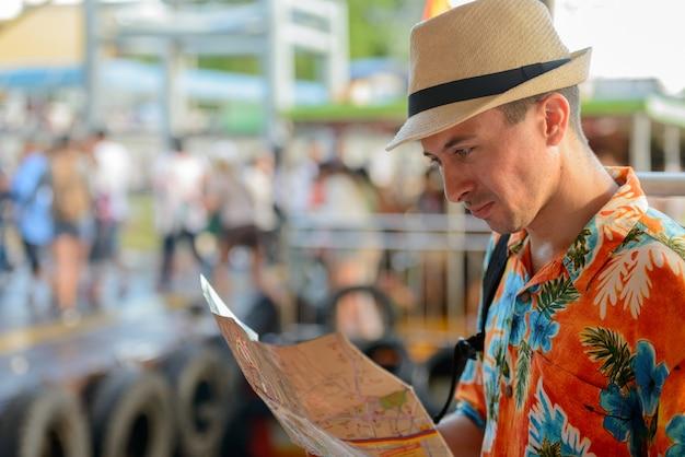 Ritratto di giovane uomo turistico bello al molo in vista del fiume nella città di bangkok