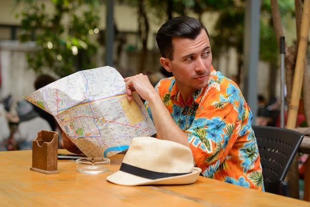 Ritratto di giovane uomo bello turista al ristorante in città all'aperto