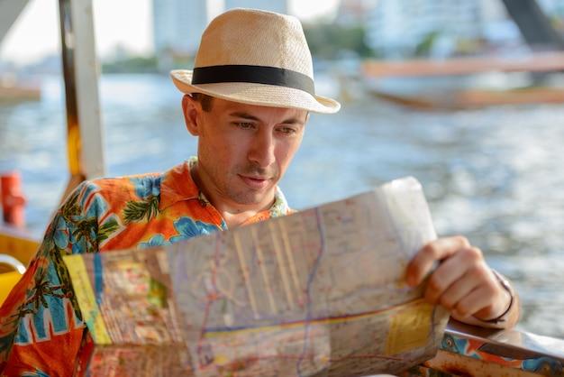 Ritratto di giovane uomo turistico bello in sella alla barca come trasporto pubblico nella città di bangkok