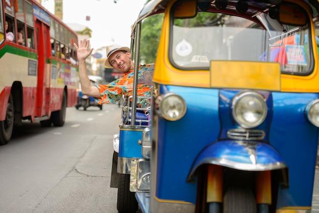 Ritratto di giovane uomo turistico bello che guida il tuk tuk come trasporto pubblico locale nella città di bangkok