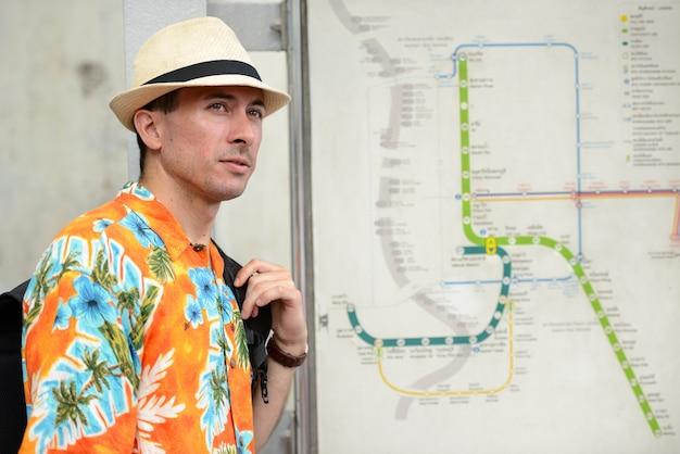 Ritratto di giovane uomo turistico bello alla stazione del treno sopraelevato della città
