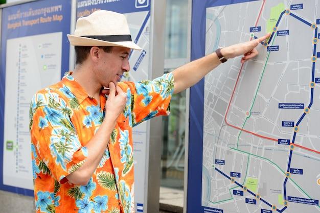 Ritratto di giovane uomo bello turistico alla stazione della metropolitana della città