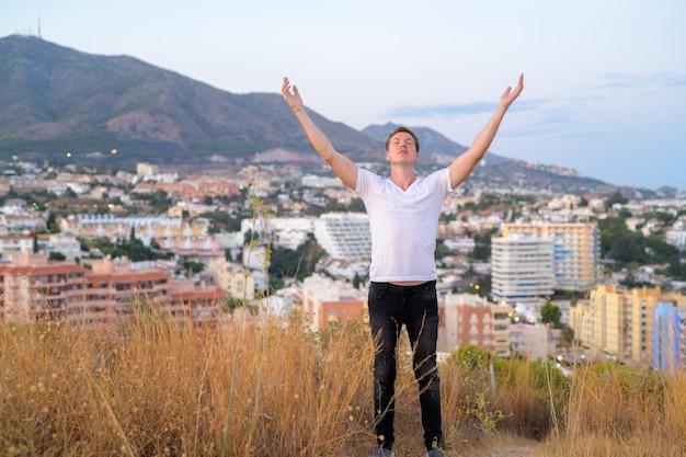 Ritratto di giovane uomo turistico bello in cima alla collina che domina la città di malaga, spagna