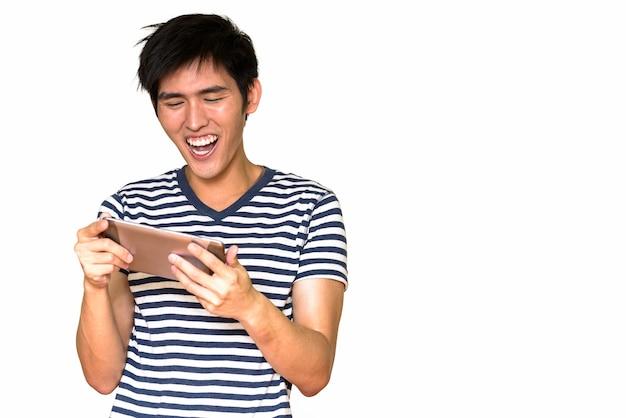 Ritratto di giovane uomo asiatico felice utilizzando la tavoletta digitale isolata contro il muro bianco