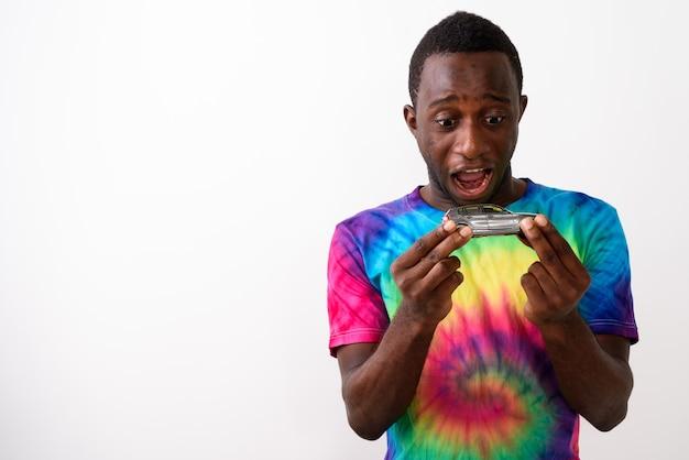 Ritratto di giovane uomo africano nero felice che tiene automobile in miniatura