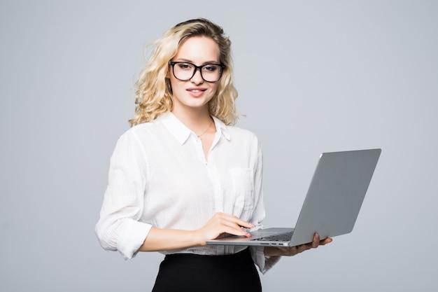 Ritratto di una giovane donna d'affari felice con un computer portatile sul muro bianco