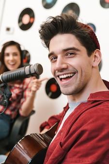 Ritratto di giovani caucasici felici che si esibiscono al programma radiofonico durante la registrazione di podcast per lo spettacolo online