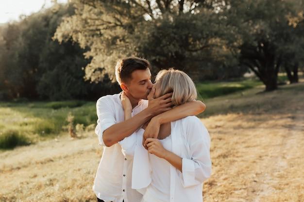 Ritratto di giovane coppia felice baci e abbracci nel parco estivo. sono vestiti con abiti bianchi.