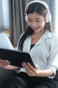 Ritratto di una giovane ragazza felice in cuffia godendo con i media di intrattenimento online con tablet nel fine settimana a casa.