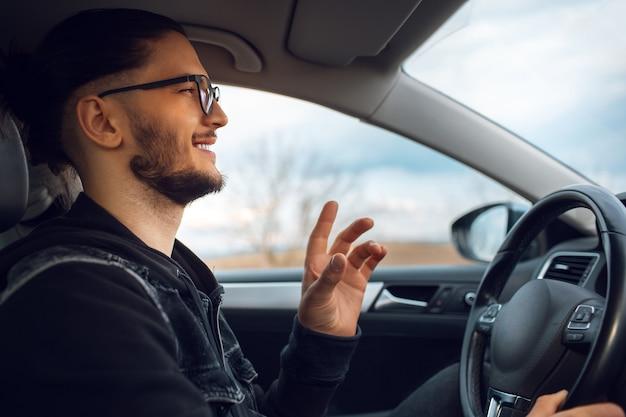 Ritratto di giovane uomo felice, che spiega qualcosa e guida l'auto