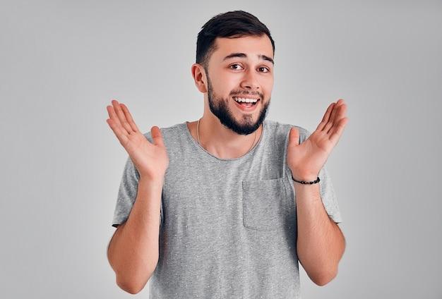 Ritratto di giovane uomo felice con le mani alzate verso l'alto
