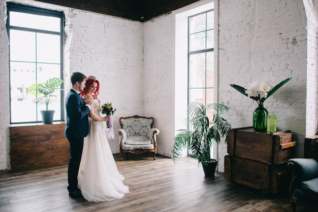 Ritratto di giovani sposi felici in una stanza in stile loft