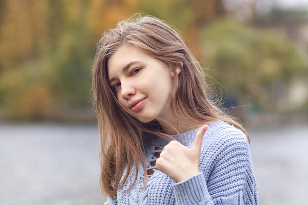 Ritratto di giovane donna positiva felice, ragazza adolescente sta mostrando il pollice in su, come, gesto di approvazione e sorridente nel parco in autunno