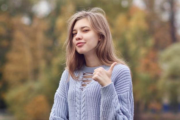 Ritratto di giovane donna positiva felice, ragazza adolescente sta mostrando il pollice in su, come, gesto di approvazione.