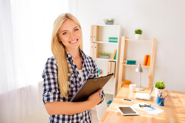 Ritratto di giovane segretaria felice azienda cartella con i documenti