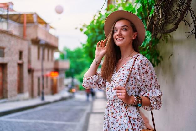 Ritratto di giovane felice sorridente carina bella bruna viaggiatore ragazza con i capelli lunghi che indossa il cappello che cammina da solo per la città al sole estivo day