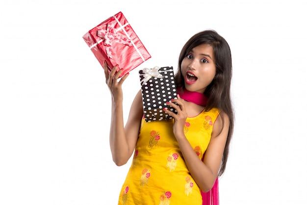 Ritratto di giovani contenitori di regalo indiani sorridenti felici della tenuta della ragazza su un fondo bianco.