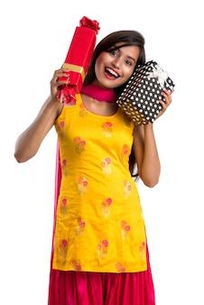Ritratto di giovane ragazza indiana sorridente felice che tiene i contenitori di regalo su uno spazio bianco.