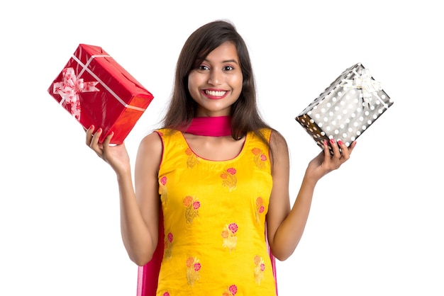 Ritratto di giovane ragazza indiana sorridente felice che tiene i contenitori di regalo su un bianco.