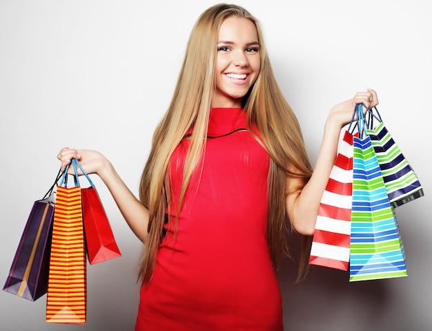 Ritratto di giovane donna sorridente felice con borse della spesa su grigio