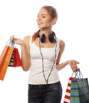 Ritratto di giovane donna sorridente felice con borse della spesa, isolato su sfondo bianco