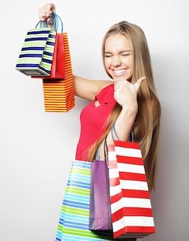 Ritratto di giovane donna sorridente felice con borse della spesa, su sfondo bianco