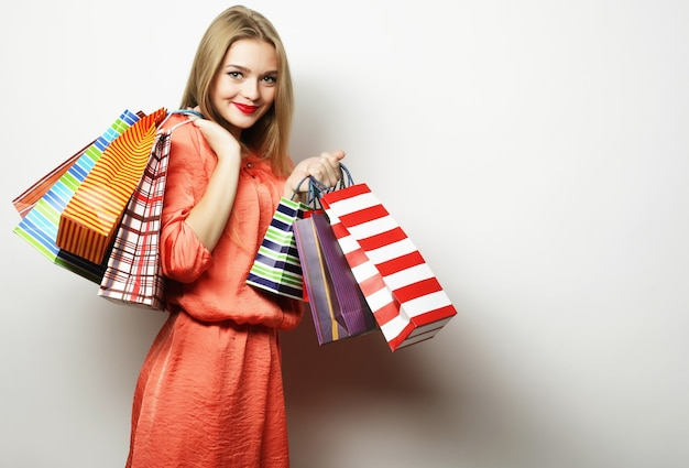 Ritratto di giovane donna sorridente felice con le borse della spesa, su sfondo bianco