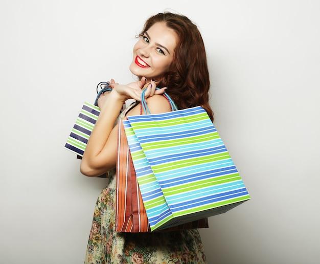 Ritratto di giovane donna sorridente felice con borse della spesa, over white