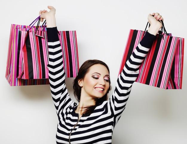 Ritratto di giovane donna sorridente felice con le borse della spesa.