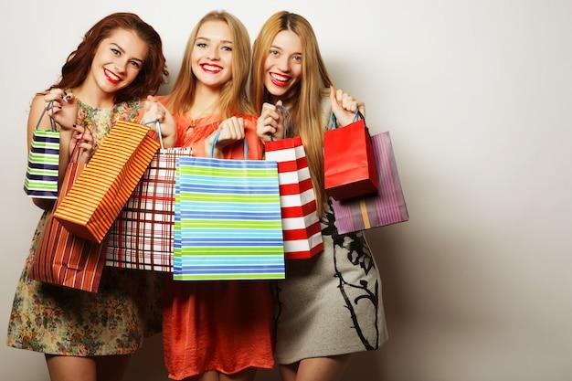 Ritratto di giovani donne sorridenti felici con borse della spesa over white