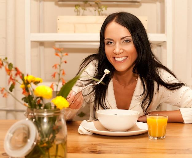 Ritratto di giovane donna felice che mangia insalata a casa