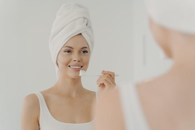 Ritratto di giovane bella donna sana con un asciugamano sulla testa dopo la doccia con un sorriso a trentadue denti mentre si lava delicatamente i denti, guardandosi allo specchio con una piacevole espressione facciale. concetto di salute dentale