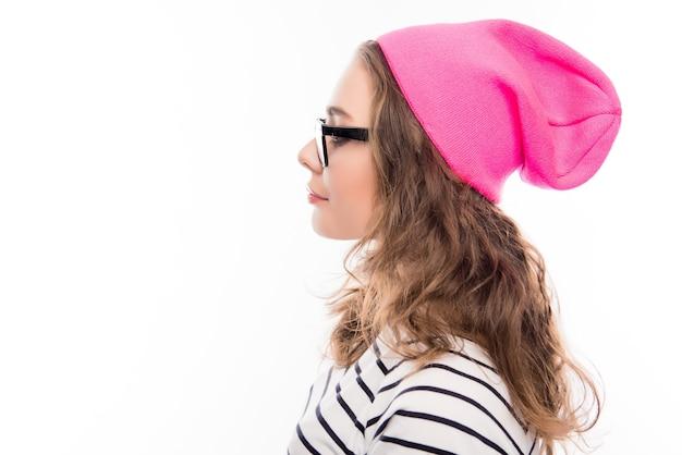Ritratto di ragazza giovane hipster in occhiali e cappello rosa