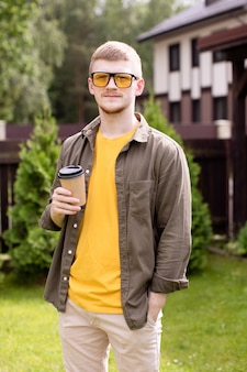 Ritratto di giovane hipster ragazzo uomo d'affari libero professionista in piedi all'aperto, che riposa nel parco con una tazza di tè, pausa caffè, studente maschio agghiacciante. estate, tempo libero, persone, concetto di persona creativa