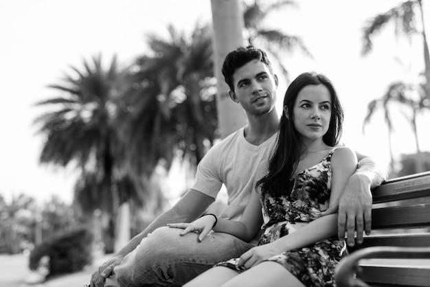 Ritratto di giovane coppia ispanica rilassante insieme nel parco