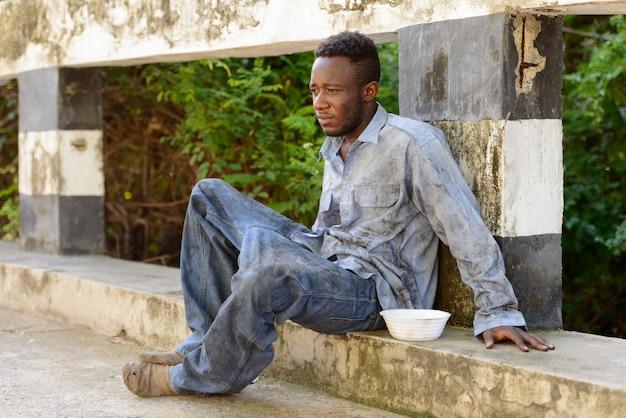 Ritratto di giovane senzatetto uomo africano sul ponte nelle strade all'aperto