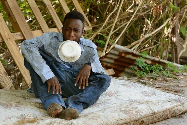 Ritratto di giovane senzatetto uomo africano nelle strade all'aperto