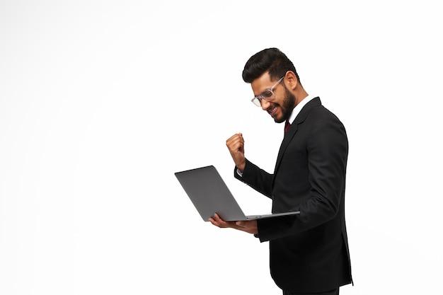 Ritratto di giovane manager indiano che usa il suo laptop e celebra la vittoria su sfondo bianco isolato