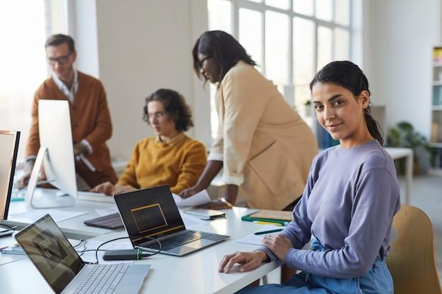 Ritratto di giovane donna indiana che guarda la telecamera mentre si utilizza il laptop in ufficio con un team diversificato di sviluppatori di software, spazio di copia