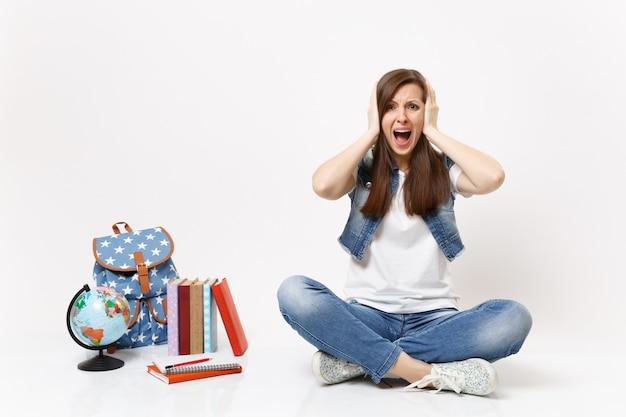 Ritratto di giovane studentessa irritata in abiti di jeans che urla coprendo le orecchie seduto vicino a globo, zaino, libri di scuola isolati su muro bianco