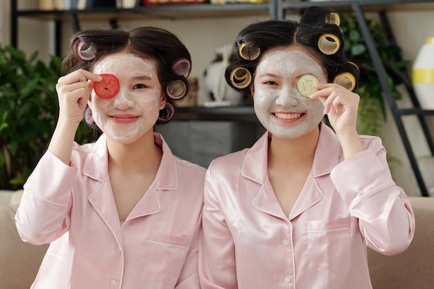Ritratto di giovani donne gioiose che applicano maschere di argilla e fette di verdure sui volti