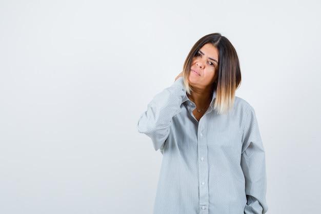 Ritratto di giovane donna che tiene la mano sul collo in una camicia oversize e sembra stanca vista frontale