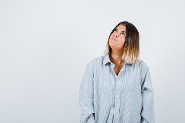 Ritratto di giovane donna che guarda in su in una camicia oversize e guarda pensierosa vista frontale
