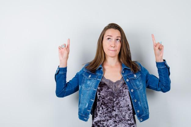 Ritratto di giovane donna che punta in camicetta, giacca di jeans e guarda una vista frontale premurosa