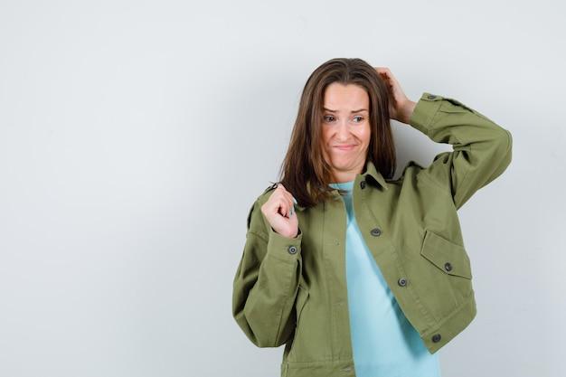 Ritratto di giovane donna che si gratta la testa in maglietta, giacca e guarda pensierosa vista frontale